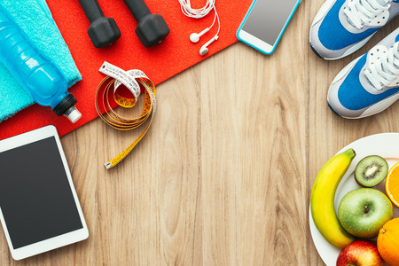 Foto de Sports and workout equipment, digital tablet and fruit on a wooden table, training and healthy lifestyle concept, flat lay - Imagen libre de derechos