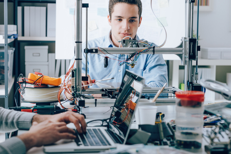 Photo pour Students sitting at the laboratory desk and using a 3D printer for prototyping - image libre de droit