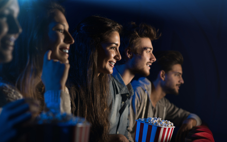 Foto de Group of teenager friends at the cinema watching a movie together and eating popcorn, entertainment and enjoyment concept - Imagen libre de derechos