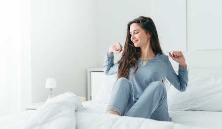 Photo pour Beautiful woman waking up in her bed in the bedroom, she is stretching and smiling - image libre de droit