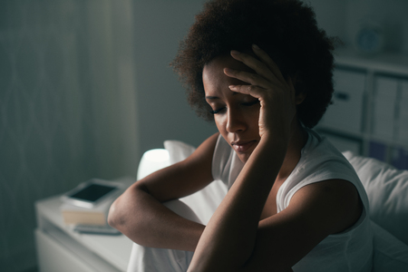 Photo pour Sad depressed woman suffering from insomnia, she is sitting in bed and touching her forehead, sleep disorder and stress concept - image libre de droit