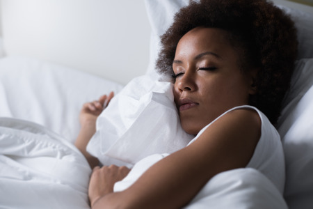 Photo pour Young african woman sleeping in her bed at night, she is resting with eyes closed - image libre de droit