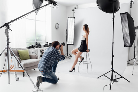 Photo for Professional photo shooting at the studio: a beautiful young model is smiling and posing; the photographer is taking pictures with a digital camera - Royalty Free Image