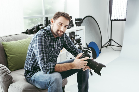 Photo for Photographer working in his studio and having a break during a photo shoot, he is holding a digital camera - Royalty Free Image