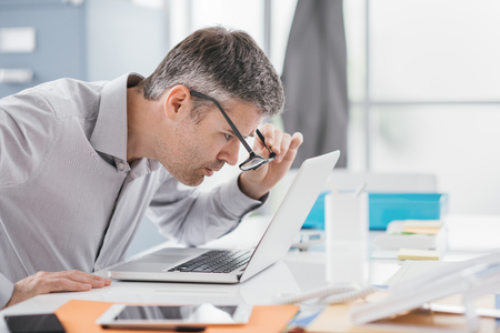 Foto de Businessman working at office desk, he is staring at the laptop screen close up and holding his glasses, workplace vision problems - Imagen libre de derechos
