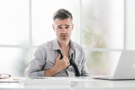 Foto de Nervous businessman working in a very hot office, he is sweating and loosening his tie - Imagen libre de derechos
