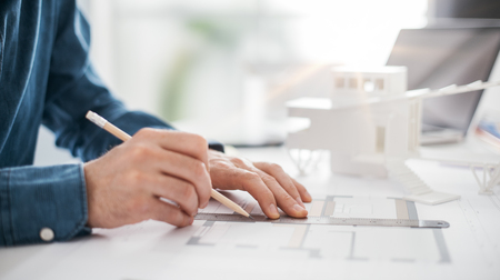Foto de Professional architect working at office desk, he is drawing and making measurements on a project blueprint, engineering and architecture concept - Imagen libre de derechos