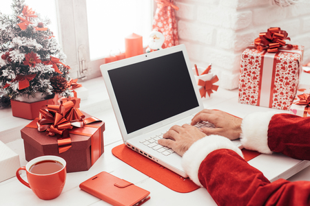 Foto de Santa Claus preparing for Christmas and connecting with a laptop, he is working at his desk at home - Imagen libre de derechos