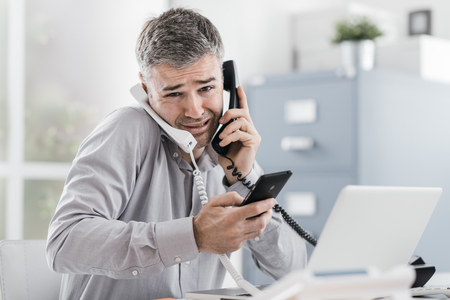 Foto de Stressed desperate businessman working in his office and having multiple calls, he is holding two handsets and a mobile phone, business management concept - Imagen libre de derechos