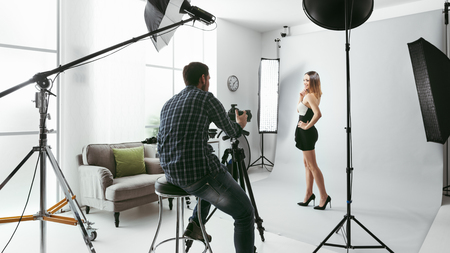 Photo for Young beautiful female model posing for a photo shoot in a studio, a photographer is shooting with a digital camera - Royalty Free Image