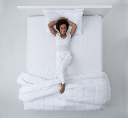 Foto de Beautiful african american woman lying in bed and smiling at camera, top view - Imagen libre de derechos