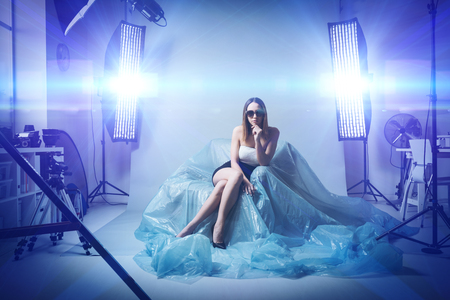 Photo for Beautiful fashion model doing a professional photo shoot, she is wearing sunglasses and an elegant dress, softboxes and flashes on the background - Royalty Free Image