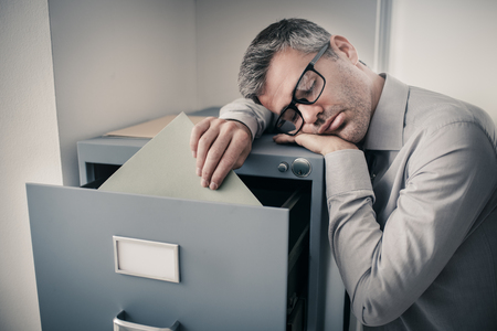 Photo pour Tired lazy office worker leaning on a filing cabinet and sleeping, he is falling asleep standing up; stress, unproductivity and sleep disorders concept - image libre de droit
