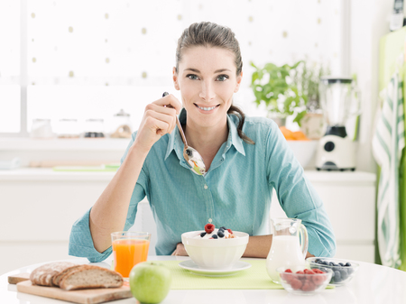 Photo pour Smiling happy woman having a relaxing healthy breakfast at home sitting at kitchen table, she is eating cereals with fruit and yogurt - image libre de droit
