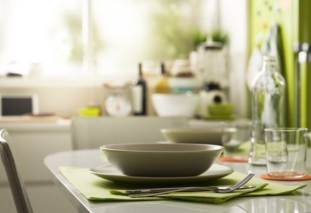 Photo for Modern kitchen interior, table setting, dishware and flatware on the foreground - Royalty Free Image
