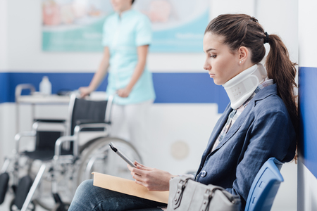 Foto de Young female patient with cervical collar support at the hospital, she is sitting in the waiting room and connecting with a digital tablet, medical staff working on the background - Imagen libre de derechos