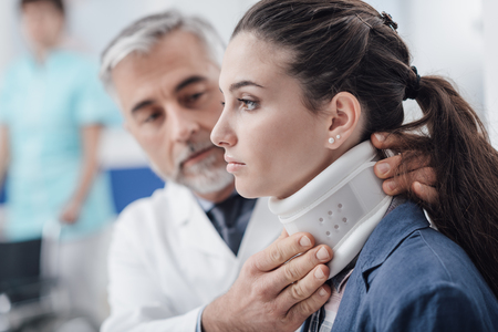 Photo pour Professional doctor visiting a young injured patient at the hospital, he is adjusting her cervical collar - image libre de droit