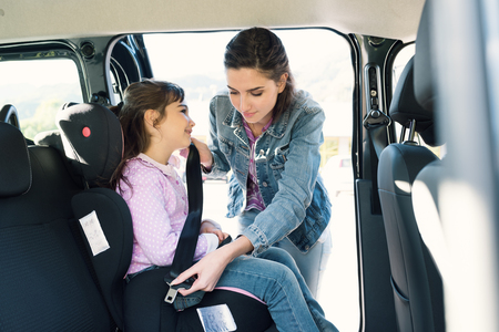 Foto de Woman helping her daughter to fasten seatbelts in the car, the girl is sitting on a safety child car seat - Imagen libre de derechos