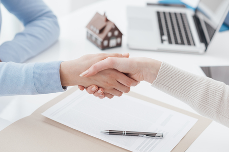 Photo pour Insurance agent and customer shaking hands after signing a contract: real estate, home loan and insurance concept - image libre de droit