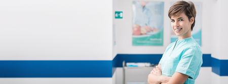 Foto de Confident young female nurse posing in the hospital aisle and smiling at camera, healthcare professionals banner - Imagen libre de derechos