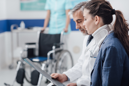 Foto de Doctor examining x-ray and medical records of an injured young patient with cervical collar and nurse pushing a wheelchair on the background - Imagen libre de derechos