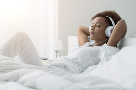 Photo for Young beautiful african american woman relaxing and listening to music using headphones, she is lying in bed - Royalty Free Image
