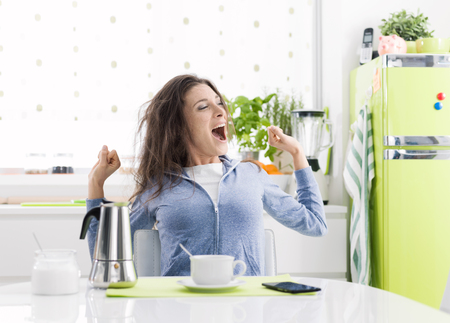 Foto de Tired lazy woman having breakfast at home in the kitchen, she is stretching and having a coffee - Imagen libre de derechos