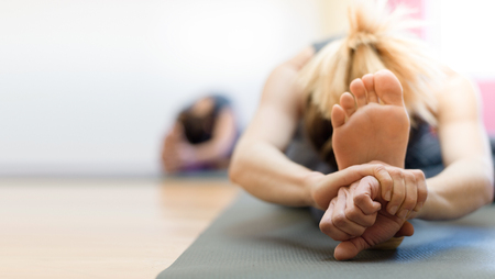 Foto de Woman doing physical exercise and stretching legs on a mat, foot close up, healthy lifestyle concept - Imagen libre de derechos