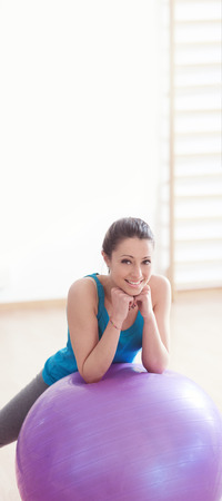 Photo for Smiling young woman working out at gym with fitness physioball. - Royalty Free Image