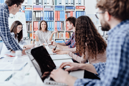 Photo for Young business team meeting in the office and brainstorming, they are discussing strategies and projects together: startups and teamwork concept - Royalty Free Image