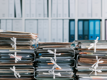 Photo for Stacks of files and paperwork in the office and bookshelves on the background: management and storage concept - Royalty Free Image
