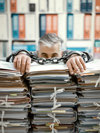 Foto de Overworked stressed businessman chained to the workplace, he is overloaded with work and lying on piles of paperwork on his desk - Imagen libre de derechos