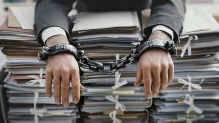 Photo pour Overworked stressed businessman chained to the workplace, he is overloaded with work and lying on piles of paperwork on his desk - image libre de droit