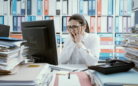 Foto de Desperate female office worker having computer problems, she is screaming and staring at the computer screen - Imagen libre de derechos