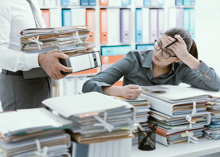 Photo for Young stressed secretary in the office overwhelmed by work and desk full of files, her boss is bringing more paperwork to her - Royalty Free Image