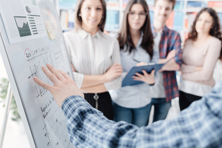 Photo for Young business team meeting and discussing a project together, a man is pointing at the whiteboard and making a presentation, startups and brainstorming concept - Royalty Free Image