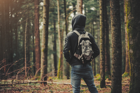Photo for Young hooded man hiking in the woods, freedom and nature concept - Royalty Free Image