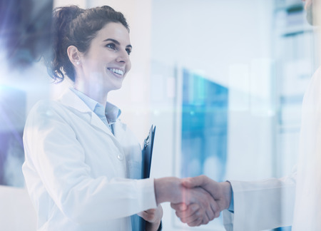 Foto de Young female practitioner shaking hands with a doctor, career and healthcare professionals concept - Imagen libre de derechos