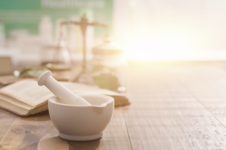 Foto de Mortar and pestle with pharmaceutical preparations's book and herbs on a wooden pharmacist table, traditional medicine and pharmacy concept - Imagen libre de derechos