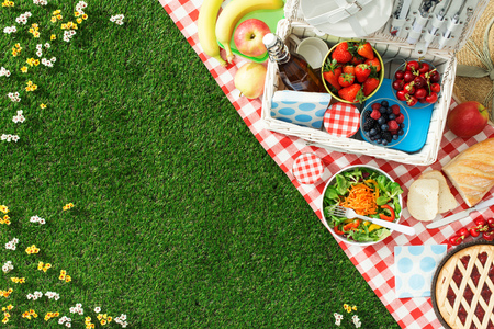 Photo for Summertime picnic setting on the grass with open picnic basket, fruit, salad and cherry pie - Royalty Free Image