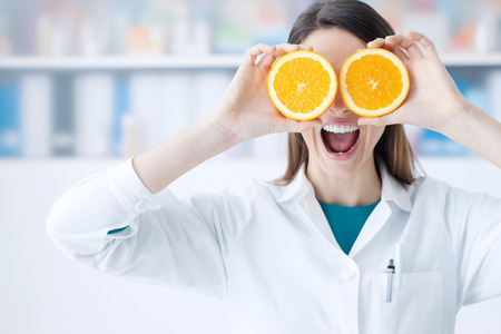 Photo for Funny female dietist holding oranges over her eyes, diet and nutrition concept - Royalty Free Image