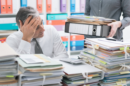Photo pour Stressed businessman working at office desk and overloaded with work, the desktop is covered with paperwork, his secretary is bringing more files - image libre de droit