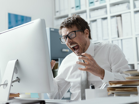 Foto de Angry business executive shouting at the computer, stressful job and system failure concept - Imagen libre de derechos
