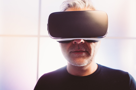 Photo pour Mature man experiencing virtual reality, he is wearing a VR headset, technology and innovation concept - image libre de droit