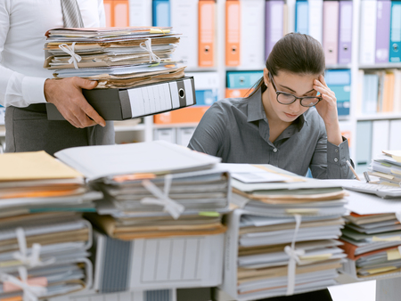 Photo pour Young stressed secretary in the office overwhelmed by work and desk full of files, her boss is bringing more paperwork to her - image libre de droit