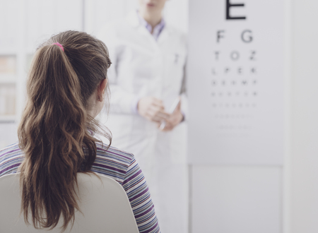 Foto de Oculist testing a young patient's eyesight using an eye chart, ophthalmology and eyesight concept - Imagen libre de derechos