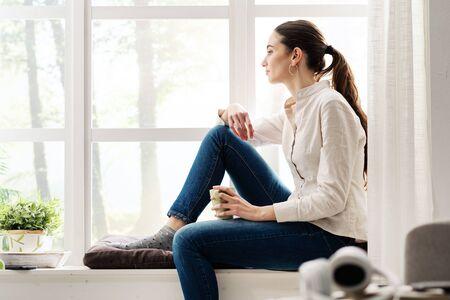 Foto de Young woman relaxing at home next to a window and having a cup of coffee - Imagen libre de derechos