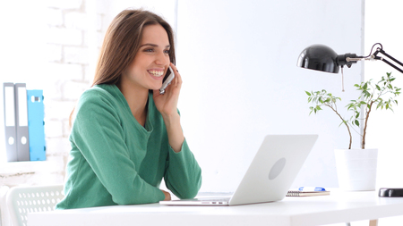Photo for Creative Woman Talking on Phone at Work, Sharing Information - Royalty Free Image