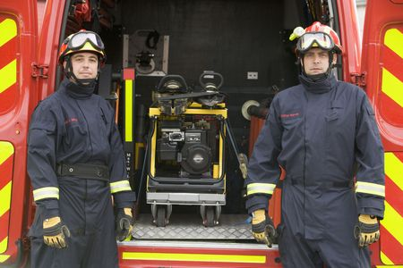 Two rescue workers standing by open back door of rescue vehicle