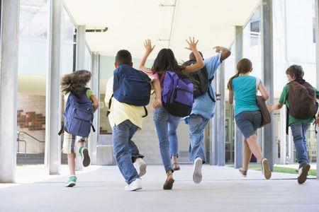 Six students running to front door of school excited